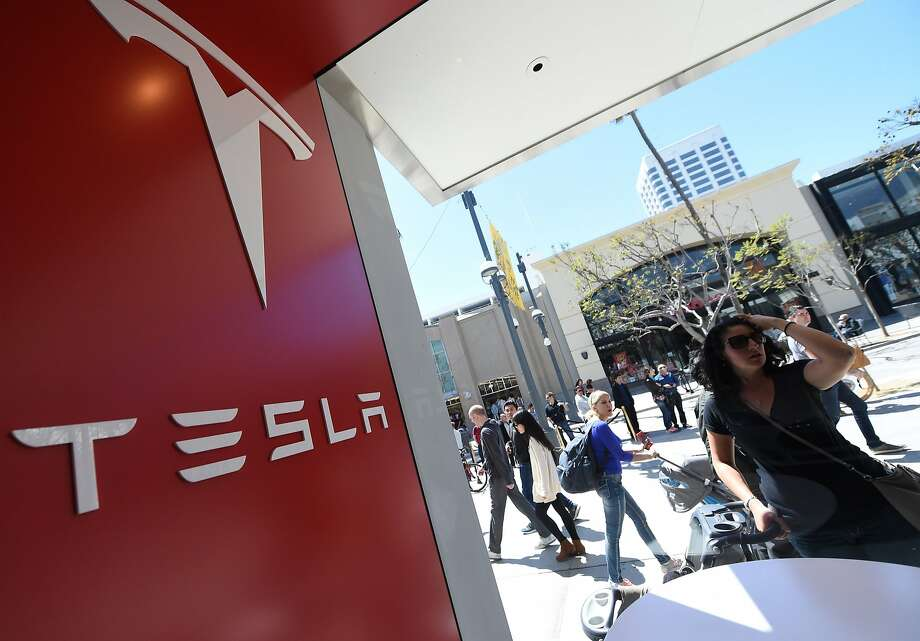 (FILES) This file photo taken on March 31, 2016 shows a woman looking into the Tesla store in Santa Monica, California. Photo: ROBYN BECK, AFP/Getty Images