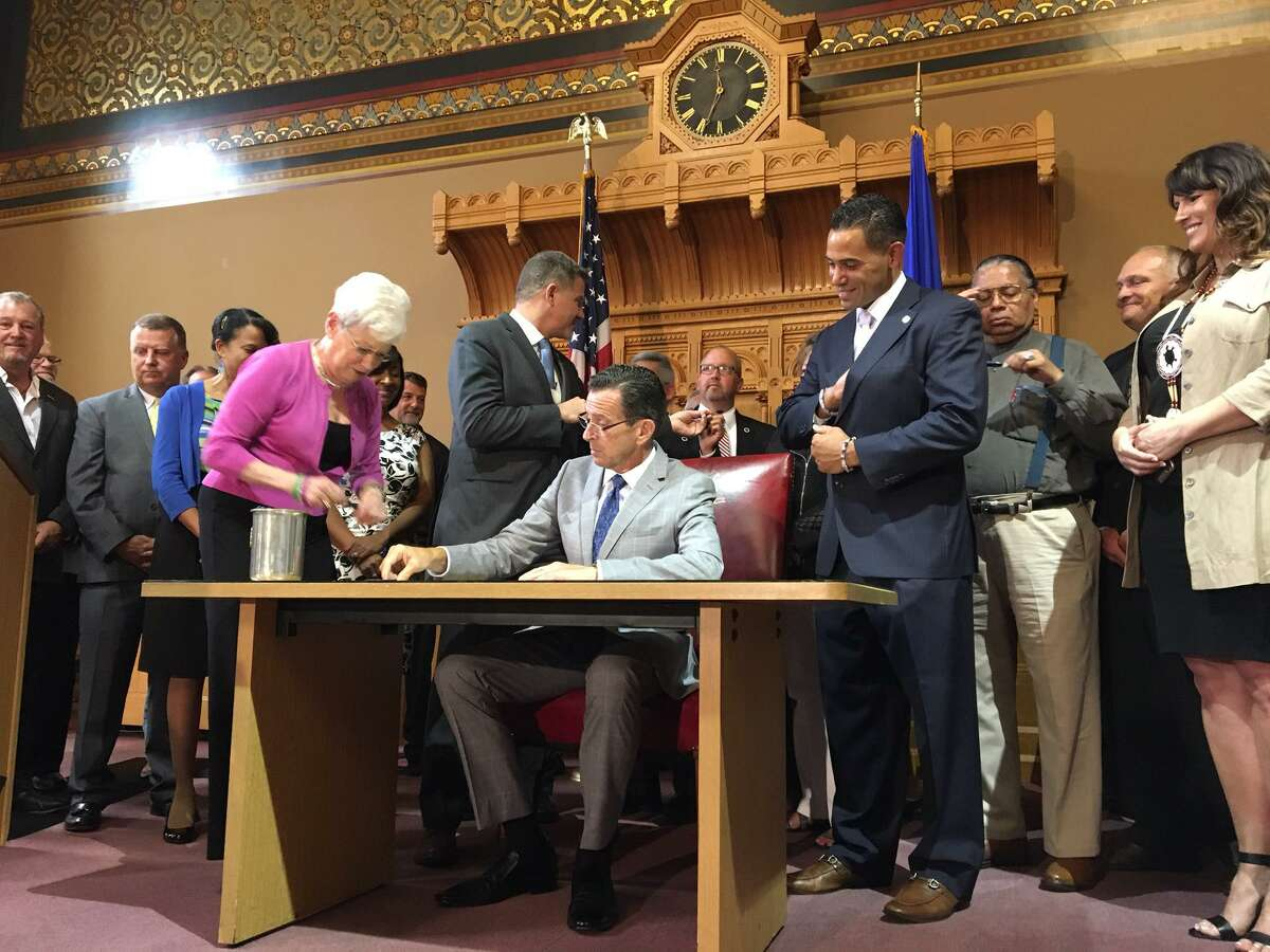 Gov. Dannel P. Malloy takes part in a ceremony commemorating his earlier approval of legislation to build a third tribal casino in Connecticut. Lt. Gov. Nancy Wyman is dishing out pens.