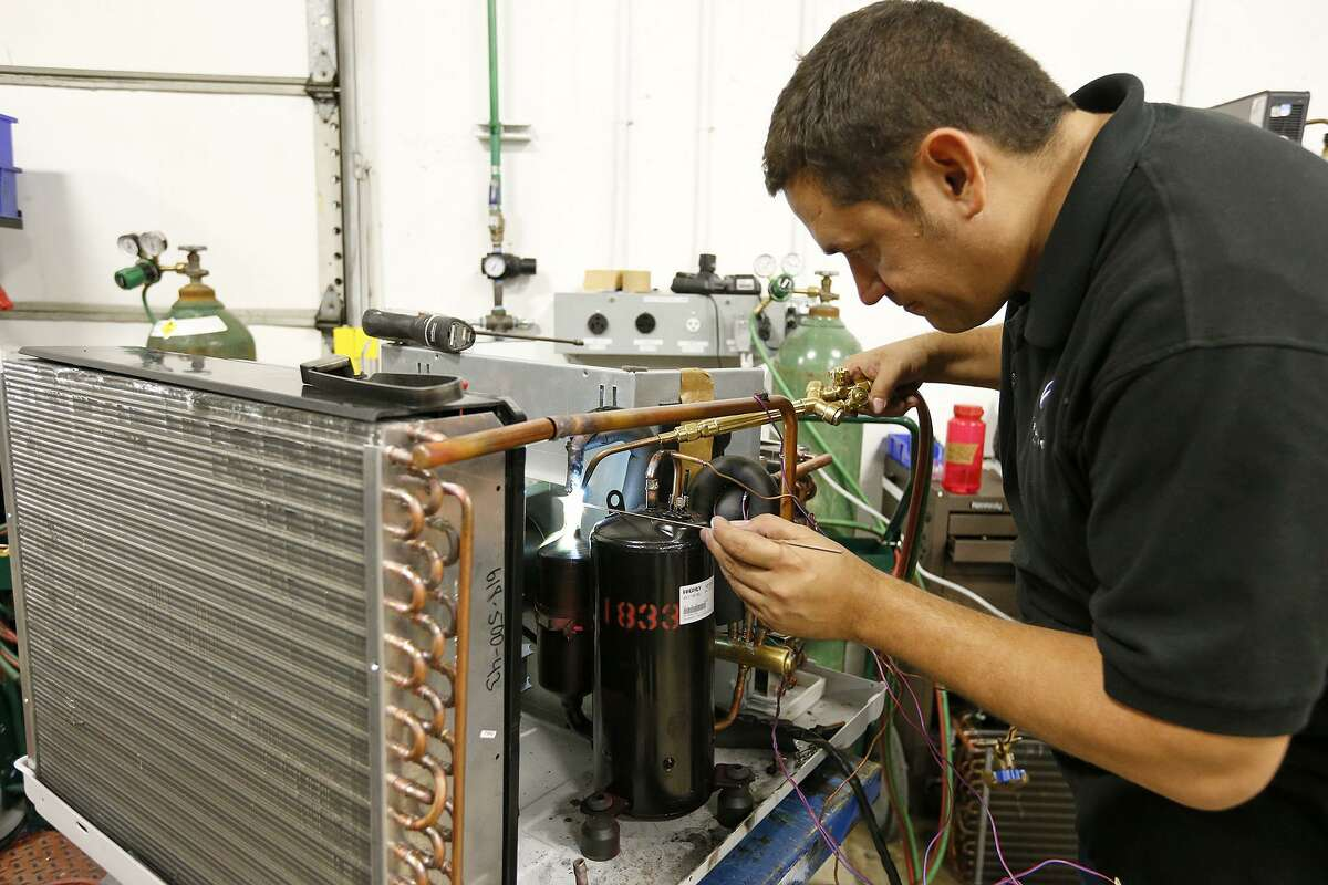 Friedrich Air Conditioning Company's Brian Sarate installs a compressor to test at the Friedrich Air Conditioning Company Design and Development Center.