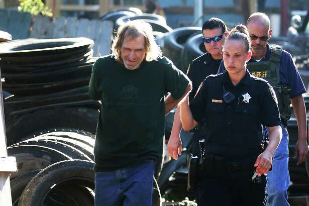 Liberty County Sheriff's deputies escort a bare-footed Robert Alen Piver at his residence located at 112 CR 6477 in the Woodland Hills subdivision of Dayton early Friday morning. His arrest, officials say, ends an 8-month nightmare for county officials and neighbors.