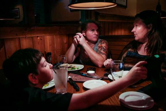 Sage Fox, 44, (center), son Gregory Evans, 10, (left) and wife Olga Evans (right) eat dinner at Outback Steakhouse in Elk Grove, Calif., on Thursday, July 27, 2017. Sage is a transgender woman and a former U.S. Army Captain. She serves in the reserves.