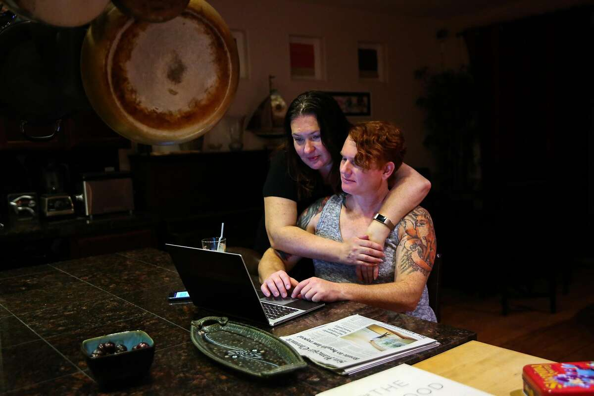 Olga Evans (left), 45, embraces wife Sage Fox, 44 (right) while reading the news and looking at social media in their kitchen in Elk Grove, Calif., on Thursday, July 27, 2017. Sage is a transgender woman and a former U.S. Army Captain. She serves in the reserves.