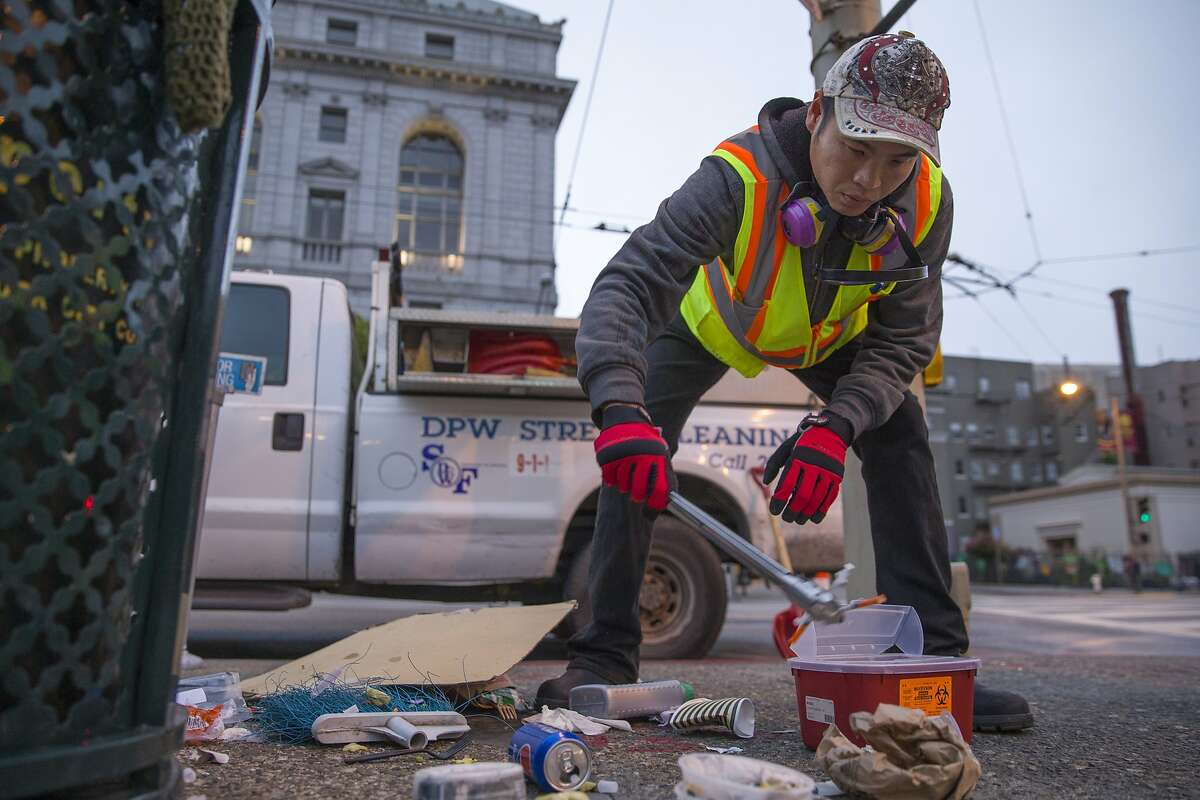 Michael Chan with S.F. Public Works disposes used needles outside City Hal on Thursday, July 27, 2017, in San Francisco, Calif.