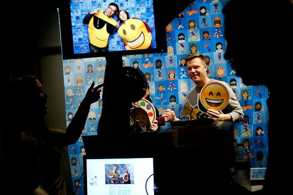 From left: Naomi Wardell takes a photo of Daniel Tate, who is holding the Smiling Face With Open Mouth and Smiling Eyes emoji at a photobooth, during the first-ever Emojicon, at the Westfield San Francisco Centre, on Saturday, Nov. 5, 2016 in San Francisco, Calif.