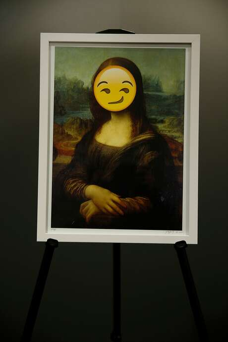 "An emoji over a copy of Leonardo da Vinci's ""Mona Lisa"" during the first Emojicon in San Francisco in November. Photo: Santiago Mejia, The Chronicle"