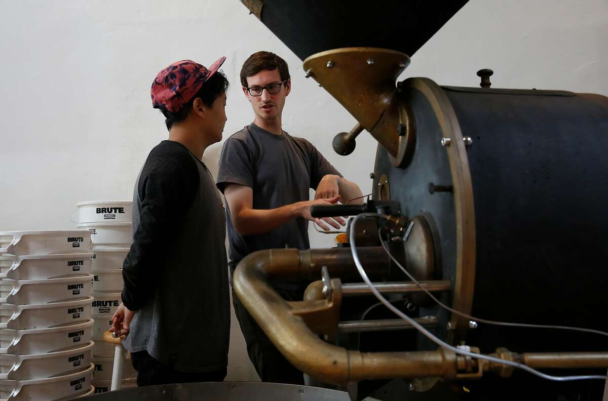 Roasting Facility Manager John Felder, right, teaches Barista and Roaster in Training Joshua Lee how to use the company's vintage German-made coffee roaster at Saint Frank coffee on Mission Street in San Francisco.