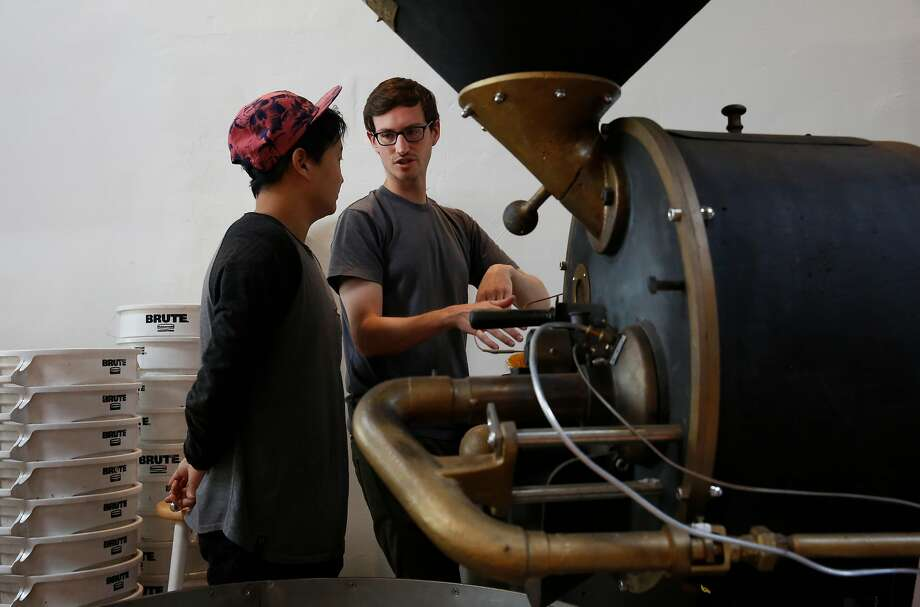 Roasting Facility Manager John Felder, right, teaches Barista and Roaster in Training Joshua Lee how to use the company's vintage German-made coffee roaster at Saint Frank coffee on Mission Street in San Francisco. Photo: Leah Millis, The Chronicle