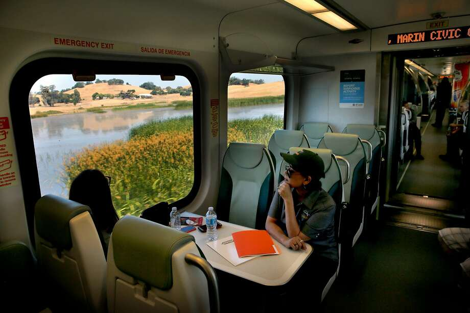 Isabella Clegg (left), a SMART train community outreach intern, and Jeanne Mariana-Belding, communications and marketing manager, enjoy the view along the way aboard the SMART train as it travels to Petaluma station. Photo: Michael Macor, The Chronicle