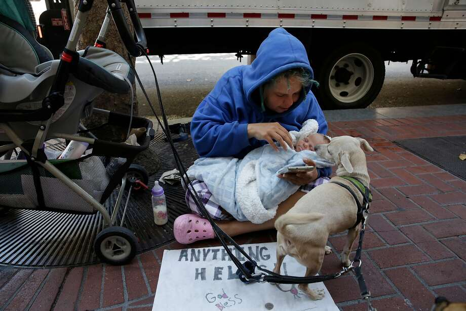 Megan Doudney tends to 2-month-old daughter Nedahlia as she panhandles on Market Street last month. Photo: Lea Suzuki, The Chronicle