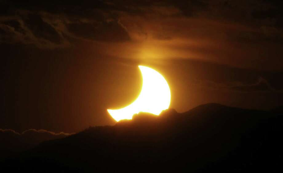 In this May 20, 2012, file photo, a solar eclipse is seen as the sun sets behind the Rocky Mountains from downtown Denver. The solar eclipse that is cutting a diagonal path across the U.S. next month will be discussed by Paul Alimena at 7:30 p.m. Wednesday  at the Perrot Memorial Library, 90 Sound Beach Ave., Old Greenwich. Free and open to the public. Photo: David Zalubowski / Associated Press / Copyright 2017 The Associated Press. All rights reserved.