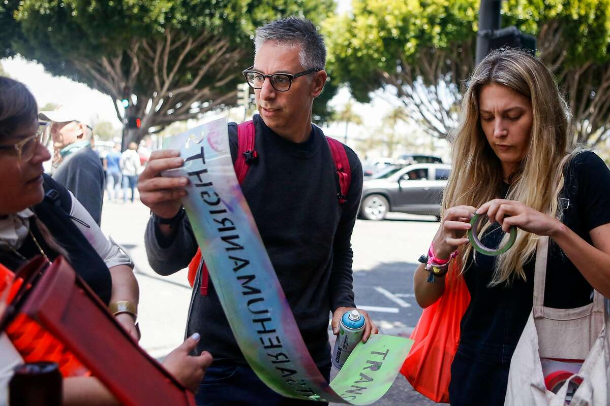 """Adam Werbach, middle, co-founder of #WTF (Win the Future), Jessica Tully, left, organizer, and Danielle Guerin, right, project manager, discuss where to set up the stencil saying """"#transrightsarehumanrights"""" outside the Armed Forces Recruiting Center in San Francisco on Friday, July 28, 2017."""