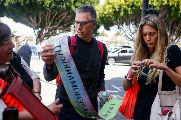 "Adam Werbach, middle, co-founder of #WTF (Win the Future), Jessica Tully, left, organizer, and Danielle Guerin, right, project manager, discuss where to set up the stencil saying ""#transrightsarehumanrights"" outside the Armed Forces Recruiting Center in San Francisco on Friday, July 28, 2017."