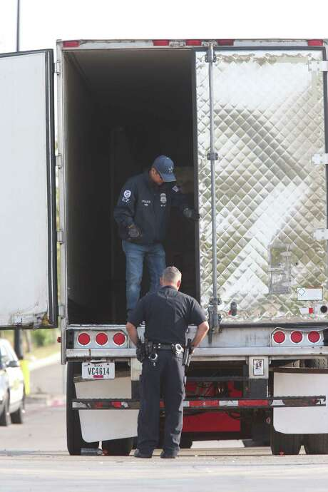 Law enforcement personnel investigate the scene where dozens of immigrants were trapped in a semi-trailer truck parked in a Walmart parking lot in San Antonio. Ten immigrants died. (Jerry Lara / San Antonio Express-News) Photo: Jerry Lara, Staff / 2017 San Antonio Express-News