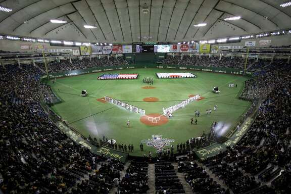 FILE - In this March 28, 2012, file photo, flags of the United States and Japan are carried during the opening ceremony at a season-opening baseball game between the Oakland Athletics and the Seattle Mariners at Tokyo Dome in Tokyo. Major League Baseball plans to start the 2019 and 2020 seasons in Asia and play regular-season games in England in June of both years. The collective bargaining agreement reached in November was finalized and sent to the clubs Friday, July 28, 2017.