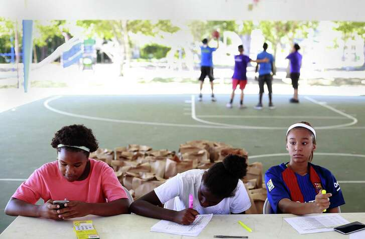 Youth Advisory Committee members Maria Williams, 11 (from left) and Deleha Williams, 14, and Good Samaritan Center intern Alyssa Enearncion, 15, wait at the school supply drive table.