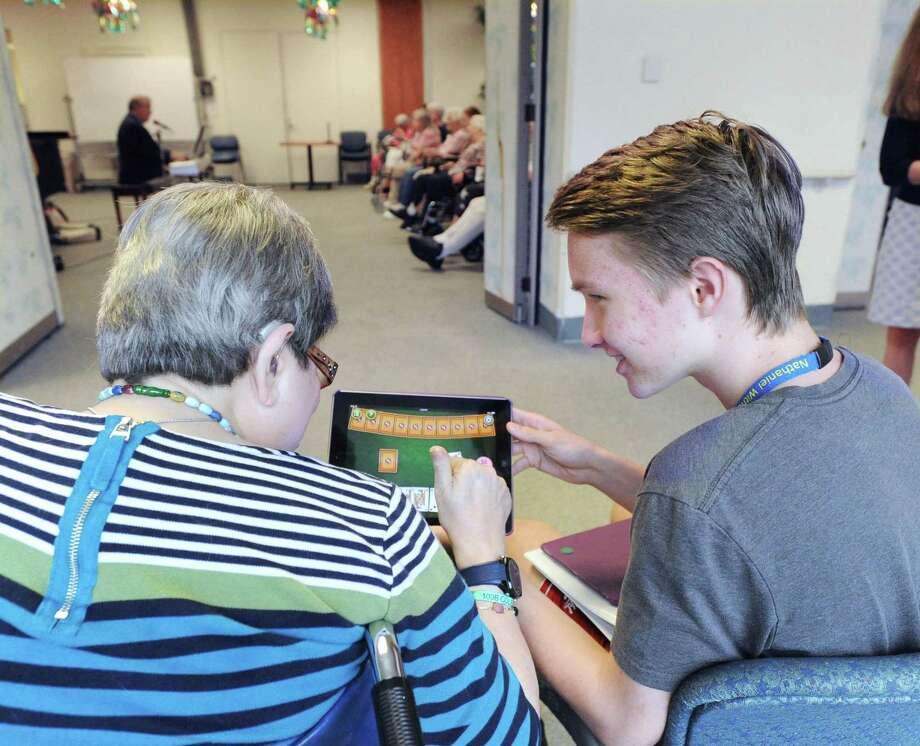 At right, Joey Farrell, 16, a Greenwich resident and a rising junior at Rye Country Day School, shows Nathaniel Witherell Nursing Home resident Dorothy Colello how to use an iPad to play the card game Gin at the town-owned short-term rehab and skilled nursing center in Greenwich, Conn., Thursday, July 27, 2017. Farrell has been spending his summer going to the Nathaniel Witherell Home to help seniors learn about technology. Photo: Bob Luckey Jr. / Hearst Connecticut Media / Greenwich Time