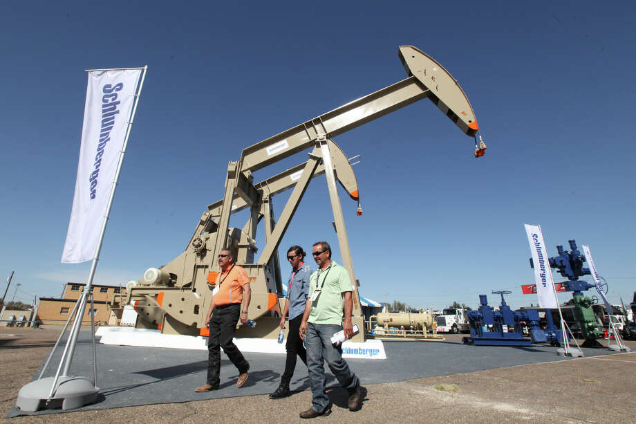 Oil show attendees walk past the Schlumberger booth at the Permian Basin International Oil Show at Ector County Coliseum on Tuesday, Oct. 18, in Odessa, Texas. (Jacob Ford/Odessa American via AP) Photo: Jacob Ford, MBO / Odessa American