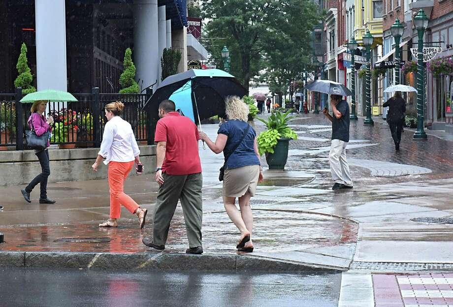 Rain caused pedestrians use umbrellas as they walk along State and Jay Streets on Thursday, July 27, 2017 in Schenectady, N.Y. (Lori Van Buren / Times Union) Photo: Lori Van Buren