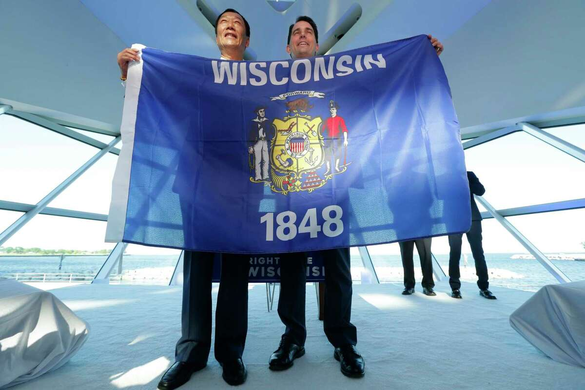Foxconn Chairman Terry Gou, left, and Gov. Scott Walker hold the Wisconsin flag to celebrate their $10 billion investment to build a display panel plant in Wisconsin, at the Milwaukee Art Museum in Milwaukee, Wis., Thursday, July 27, 2017. (Mike De Sisti/Milwaukee Journal-Sentinel via AP) ORG XMIT: WIMIL401