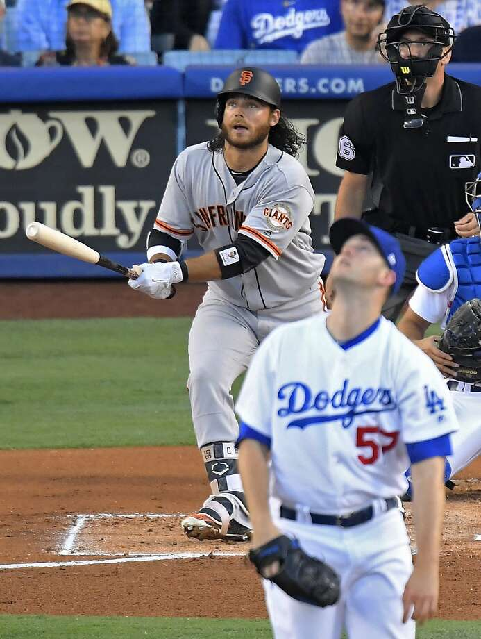 Brandon Crawford and Alex Wood watch the flight of Crawford's second-inning solo homer. Photo: Mark J. Terrill, Associated Press