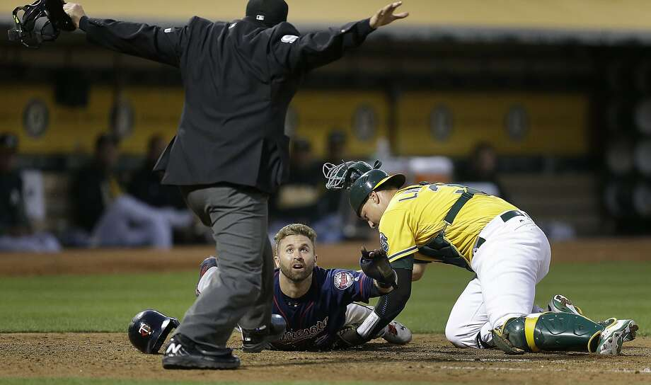 Minnesota Twins' Brian Dozier looks to home plate umpire Mark Ripperger for the call as he scores past Oakland Athletics catcher Ryan Lavarnway, right, during the fourth inning of a baseball game Friday, July 28, 2017, in Oakland, Calif. (AP Photo/Ben Margot) Photo: Ben Margot, Associated Press