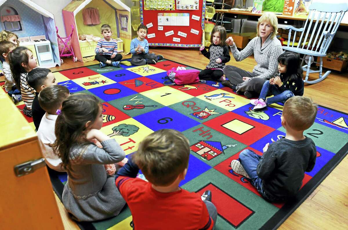 Sarah Noyes, a teacher at the Orange Congregational Church Nursery School, chats with her nursery school class of 4- to 5-year-olds, last week. The church nursery school is celebrating its 50th anniversary.