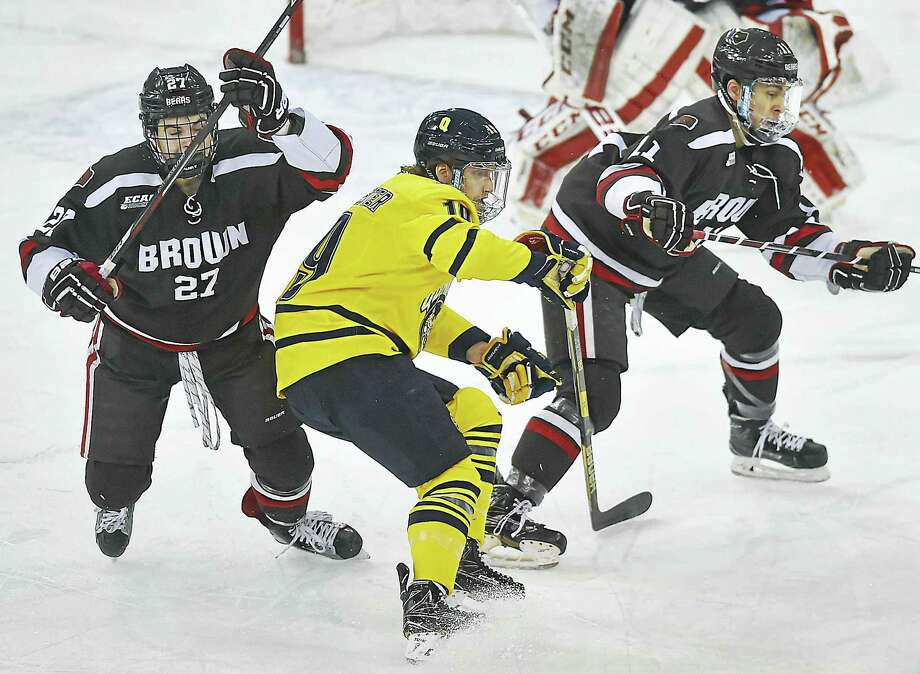 Quinnipiac forward Tanner MacMaster, center, battles Brown forward Trey Dodd (27) and defenseman Max Gottlieb during Saturday's game in Hamden. Photo: Catherine Avalone — Register   / Catherine Avalone/New Haven Register