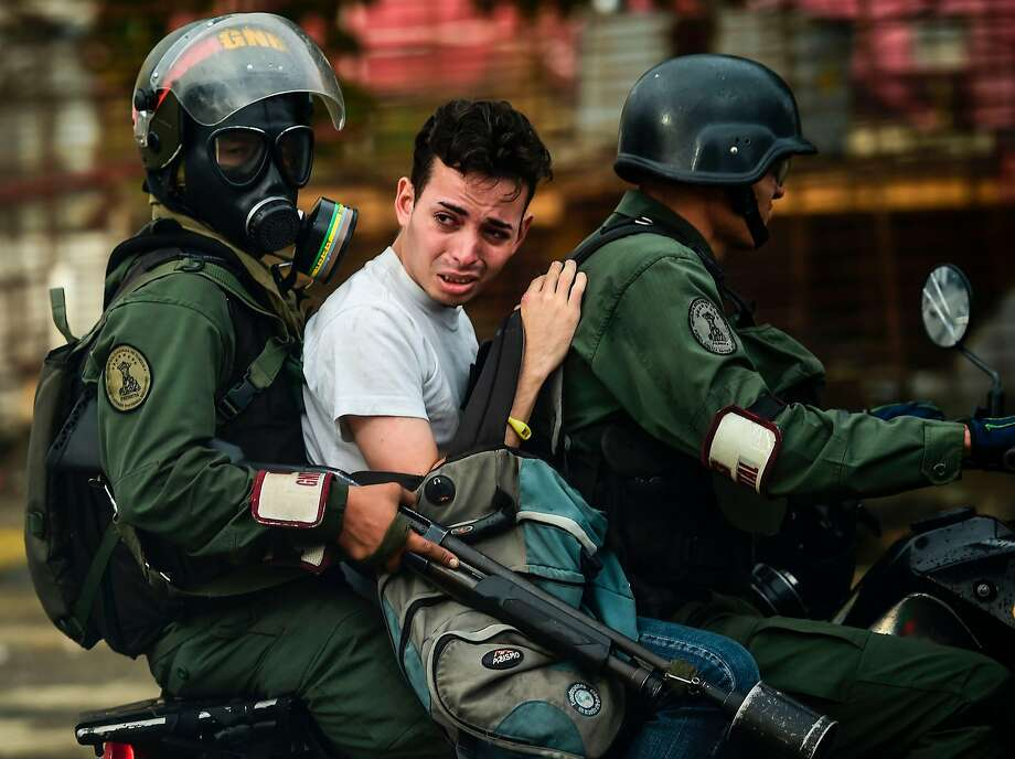 An antigovernment activist is arrested during clashes Friday in Caracas. More than 110 people have been killed in recent clashes. Photo: RONALDO SCHEMIDT, AFP/Getty Images
