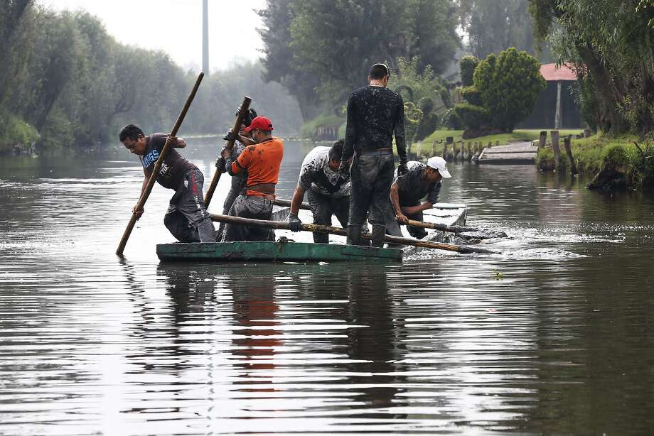 "Workers remove mud from a shallow canal in Mexico City's Xochimilco ""floating gardens"" on July 13. Fecal coliform contamination affects water fed into the canals by a treatment plant. Photo: Marco Ugarte, Associated Press"