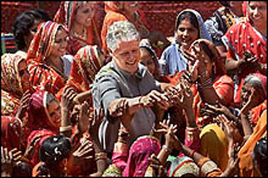 Engulfed in a celebration to honor his visit, President Clinton laughs as he reaches out to women of the village of Nayla, India, Thursday, March 23, 2000. The president had come to the village near the city of Jaipur to praise the women for their progress in economic, social and political empowerment. (AP Photo/J. Scott Applewhite) Photo: AP / AP