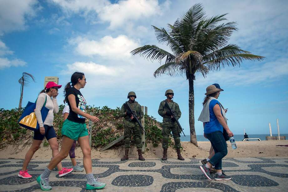 Brazilian Army soldiers stand guard at Ipanema beach after the government's decision to deploy troops to Rio de Janeiro to quell violence. Photo: MAURO PIMENTEL, AFP/Getty Images
