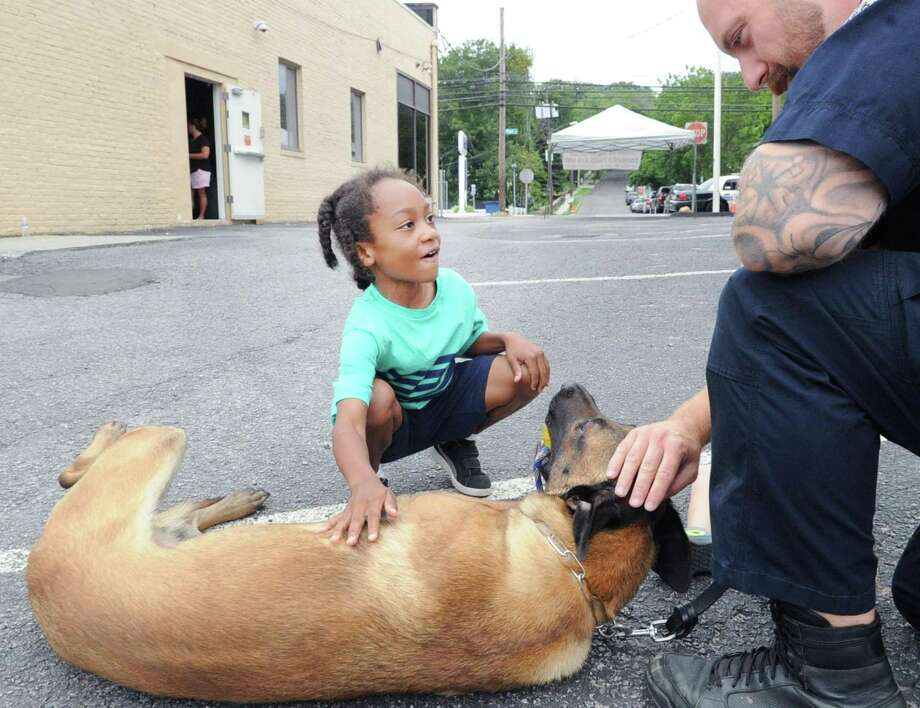 "Malachi Johnson, 7, of Stamford pets Stamford Police dog Loki, a Belgian Malinois belonging to Stamford Police K-9 officer Logan Pavia, right, during the Stamford Elks Lodge 899 fundraiser for the Stamford Police Department K-9 Unit at the lodge on Hope Street in Stamford, Conn., Saturday Morning, July 29, 2017. Marie Malwitz the exalted ruler for the lodge said ""we feel the K-9 dogs and their police handlers don't get the recogntion they deserve. They do such a great job. My favorite dog is sergeant Phelna's dog. What a beauty."" Malwitz said this is the fourth year they have held the event and on averaged each yeat have raised about $3,500 for the Stamford Police Department K-9 Unit.  Sergeant Seth O'Brien who is in charge of the five officer five dog unit said ""We are grateful for the support from the lodge and grateful for the opportunity to interact with the community."" Photo: Bob Luckey Jr. / Hearst Connecticut Media / Greenwich Time"