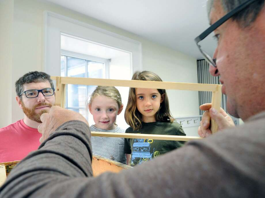 "At right, Greenwich beekeeper Jeff Brown of the Back Yard Beekeepers Association teaches ""Honey Spinning""  to Cos Cob resident Marc Lissauer, left, Marc's daughter Briar, 6, second from left, and Zoe Garros, also 6, at the Audubon Center in Greenwich, Conn., Saturday, July 29, 2017. Honey spinning is the process of harvesting honey into a finished product. Brown was there with three members of his beekeeping family to teach the process of removing the honey from the honey-combed frames and spinning it into jarable honey. Photo: Bob Luckey Jr. / Hearst Connecticut Media / Greenwich Time"
