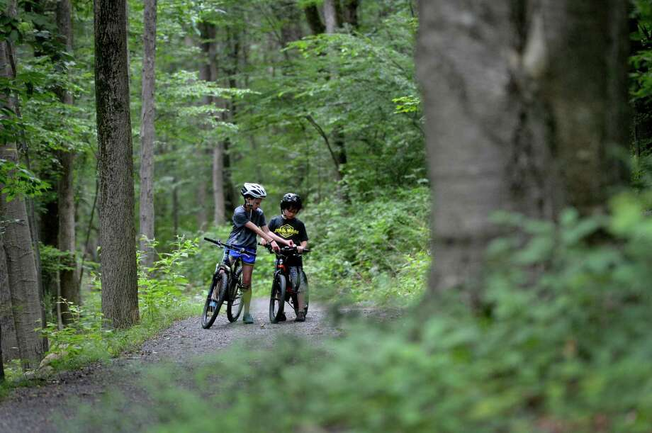Ava Malagisi, 11, of Ridgefield, helps her younger brother Max get the bell on his bicycle to ring while riding on the Norwalk River Valley Trail while their mother walks ahead Tuesday, July 25. Photo: Alex Von Kleydorff / Hearst Connecticut Media / Norwalk Hour