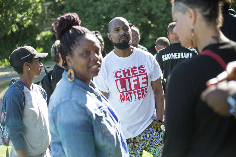 Andre Taylor, brother of Che Taylor, also killed by police, visits with mayoral candidate Nikkita Oliver and other attendees. Photo: GRANT HINDSLEY, SEATTLEPI.COM / SEATTLEPI.COM