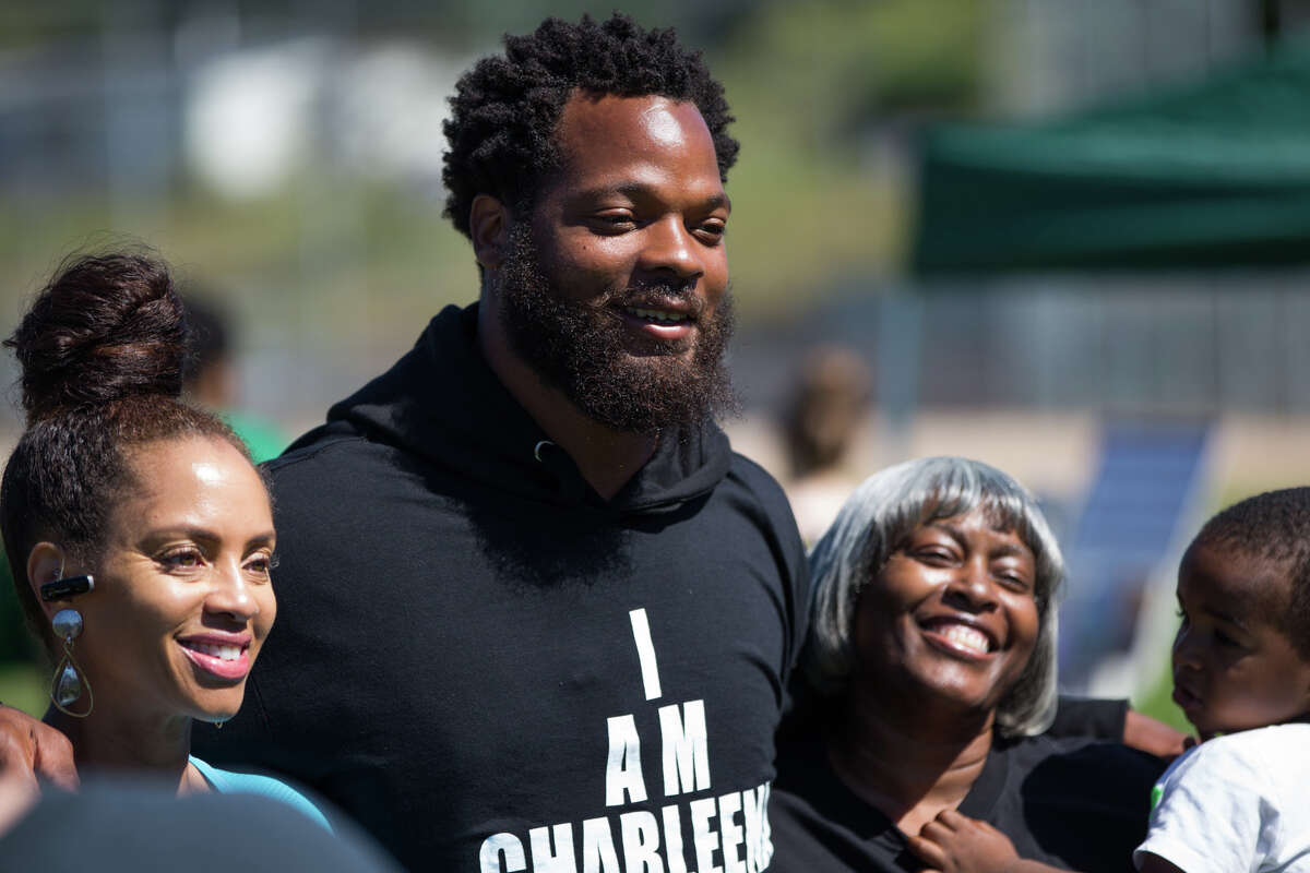 Seahawks' Michael Bennett poses with fans during a rally for Charleena Lyles and her family at Judkins Park on Saturday, July 29, 2017.