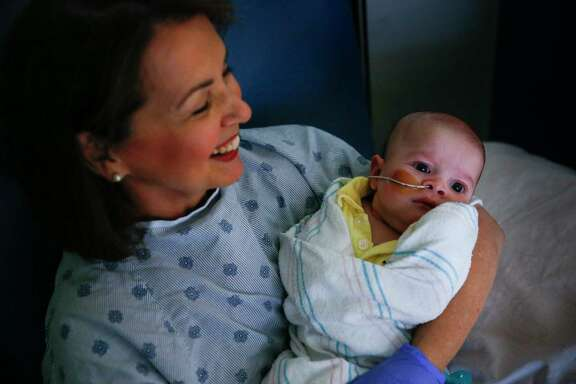 Nancy Baycroft, a volunteer baby rocker at Texas Children's Hospital, holds 3-month-old Walter Omar Pineda-Real.