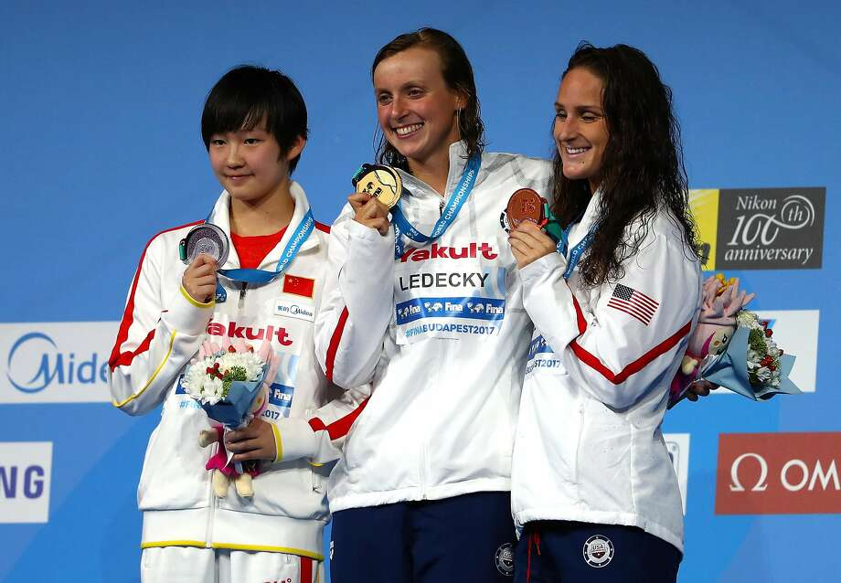 Stanford's Katie Ledecky (center) shows her gold medal for the 800-meter fresstyle. China's Bingjie Li (left) won silver and American Leah Smith bronze. Photo: Clive Rose, Getty Images