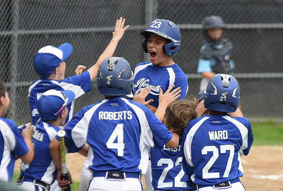Norwalk's Charlie Lafreniere, center, is greeted by teammates after his two-run first-inning home run helped stake his team to a six-run lead in Saturday's Cal Ripken Baseball 11-year-old New England opener against Franklin, Mass., at Beckwith Park in Dover, N.H. Photo: John Nash/Hearst Media Connecticut
