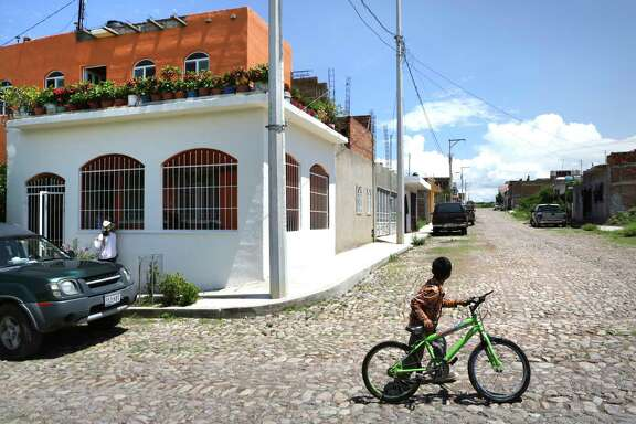A boy walks his bike up a stone street in the neighborhood of La Antorcha, home of two of the victims of the human smuggling trailer, in Calvillo, Mexico, a town west of Aguascalientes.