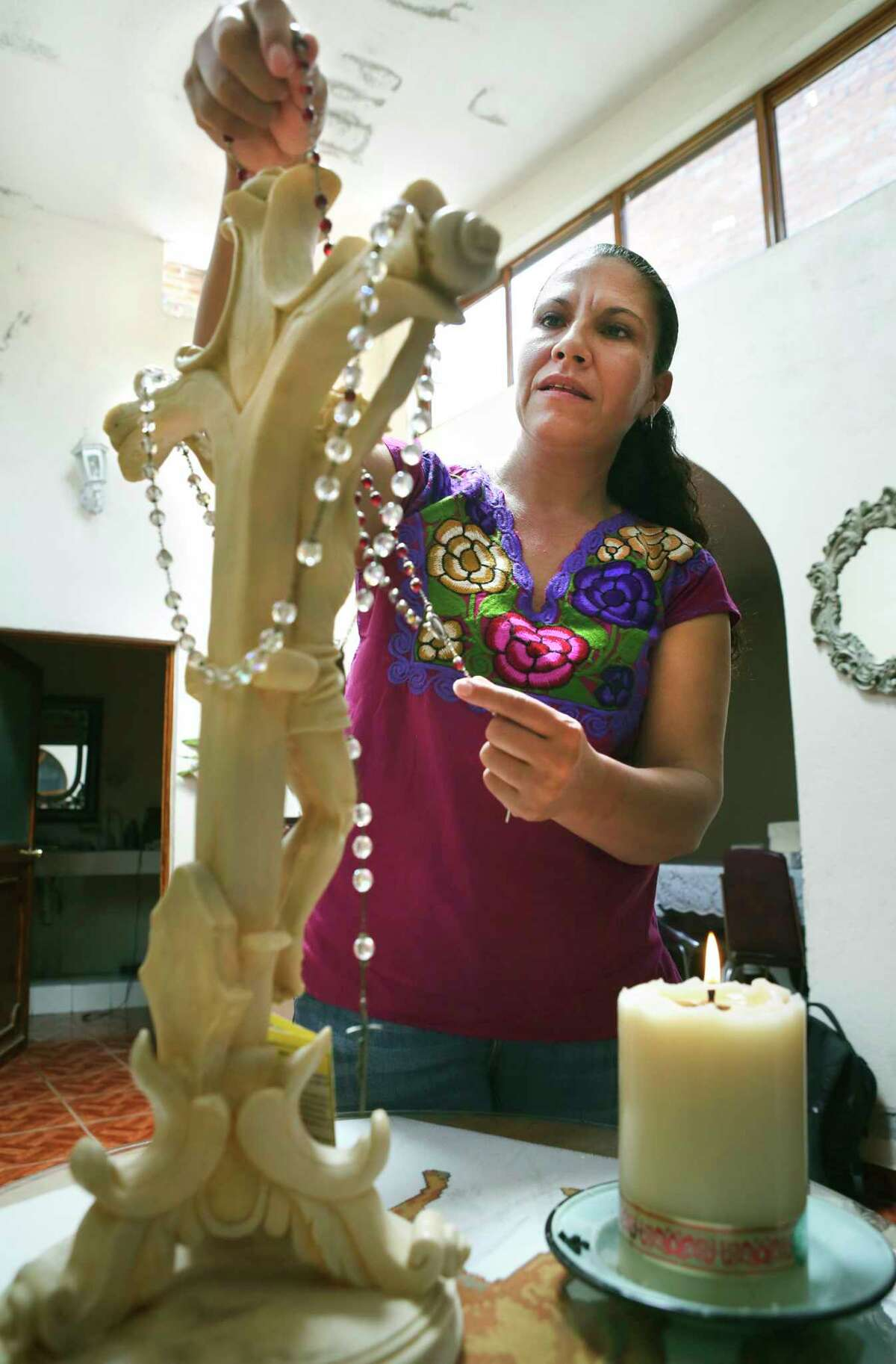 Maria Guadalupe Martinez Vargas, mother of Jose, who made it out of the human smuggling trailer, prays daily for her son with her rosary at a small shrine in her home in Calvillo, Mexico, a town west of Aguascalientes.