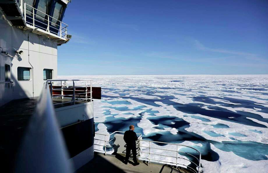 Canadian Coast Guard Capt. Victor Gronmyr looks out over the ice covering the Victoria Strait as the Finnish icebreaker MSV Nordica traverses the Northwest Passage through the Canadian Arctic Archipelago.  Sea ice that foiled famous explorers has slowly been melting away in one of the most visible effects of global warming. Photo: David Goldman, STF / Copyright 2017 The Associated Press. All rights reserved.