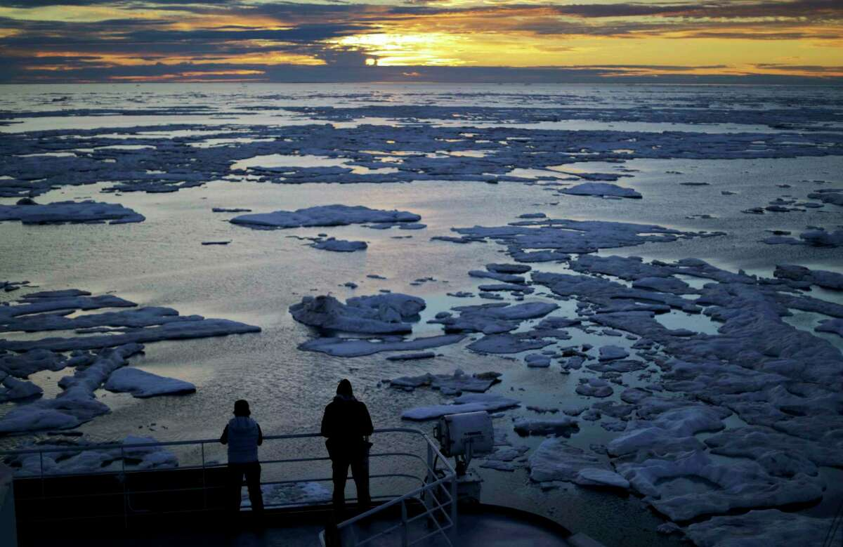 FILE - In this July 21, 2017 file photo, researchers look out from the Finnish icebreaker MSV Nordica as the sun sets over sea ice floating on the Victoria Strait along the Northwest Passage in the Canadian Arctic Archipelago. After 24 days at sea and a journey spanning more than 10,000 kilometers (6,214 miles), the Finnish icebreaker MSV Nordica has set a new record for the earliest transit of the fabled Northwest Passage. The once-forbidding route through the Arctic, linking the Pacific and the Atlantic oceans, has been opening up sooner and for a longer period each summer due to climate change. Sea ice that foiled famous explorers and blocked the passage to all but the hardiest ships has slowly been melting away in one of the most visible effects of man-made global warming.(AP Photo/David Goldman, File)