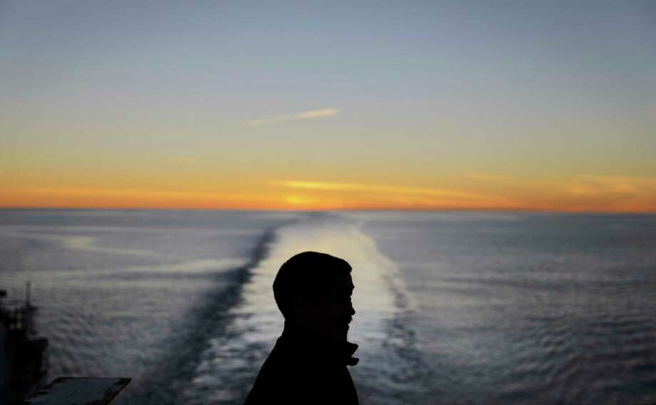 FILE - In this July 28, 2017 file photo, the sun dips below the horizon at midnight as trainee Maatiusi Manning takes in the view from aboard the Finnish icebreaker MSV Nordica as it sails toward Greenland after traversing the Northwest Passage through the Canadian Arctic Archipelago.  After 24 days at sea and a journey spanning more than 10,000 kilometers (6,214 miles), the Finnish icebreaker MSV Nordica has set a new record for the earliest transit of the fabled Northwest Passage.  The once-forbidding route through the Arctic, linking the Pacific and the Atlantic oceans, has been opening up sooner and for a longer period each summer due to climate change. Sea ice that foiled famous explorers and blocked the passage to all but the hardiest ships has slowly been melting away in one of the most visible effects of man-made global warming.  (AP Photo/David Goldman, File) Photo: David Goldman, STF / Copyright 2017 The Associated Press. All rights reserved.