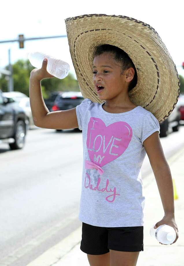 Des'Marie Hemphill uses a sombrero hat for shade as she sells bottles of cold water in the 100 degree air at the corner of Goliad and SE Military on July 29, 2017.  She was helping herd dad in a benefit effort for Texas Bad Boys Youth Football. Photo: Tom Reel, Staff / San Antonio Express-News / 2017 SAN ANTONIO EXPRESS-NEWS