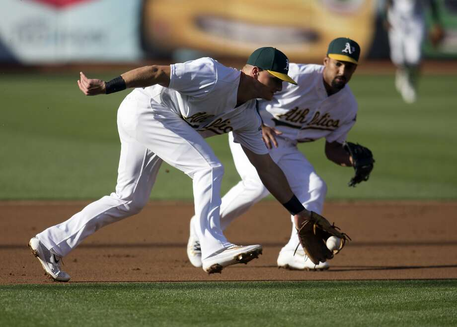 Oakland Athletics' Matt Chapman (26) cuts in front of Marcus Semien to field a grounder by Minnesota Twins' Miguel Sano during the first inning of baseball game Saturday, July 29, 2017, in Oakland, Calif. Sano was out at first.(AP Photo/D. Ross Cameron) Photo: D. Ross Cameron, Associated Press