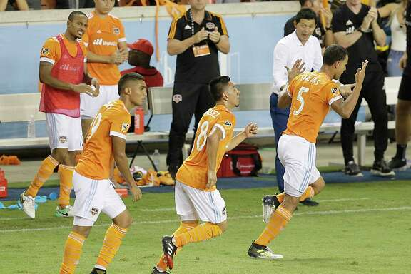 The Dynamo's Juan David Cabezas, right, celebrates with teammate Memo Rodriguez after Cabezas' goal in the 82nd minute tied the game against Portland.