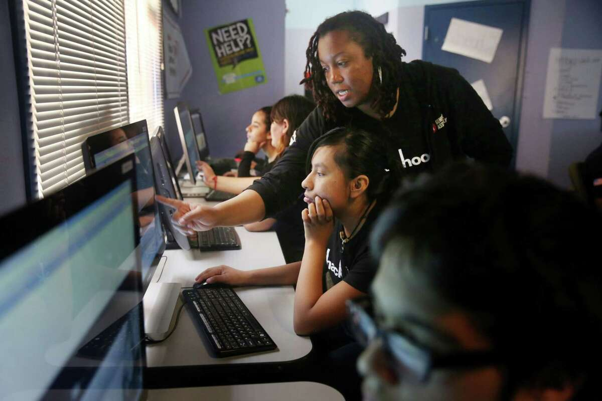 Lyn Muldrow (center standing), program director and lead instructor, gives direction to Jackie Baltierra (center sitting), 16, of Redwood City as students work on their websites during Hack the Hood boot camp in East Palo Alto.