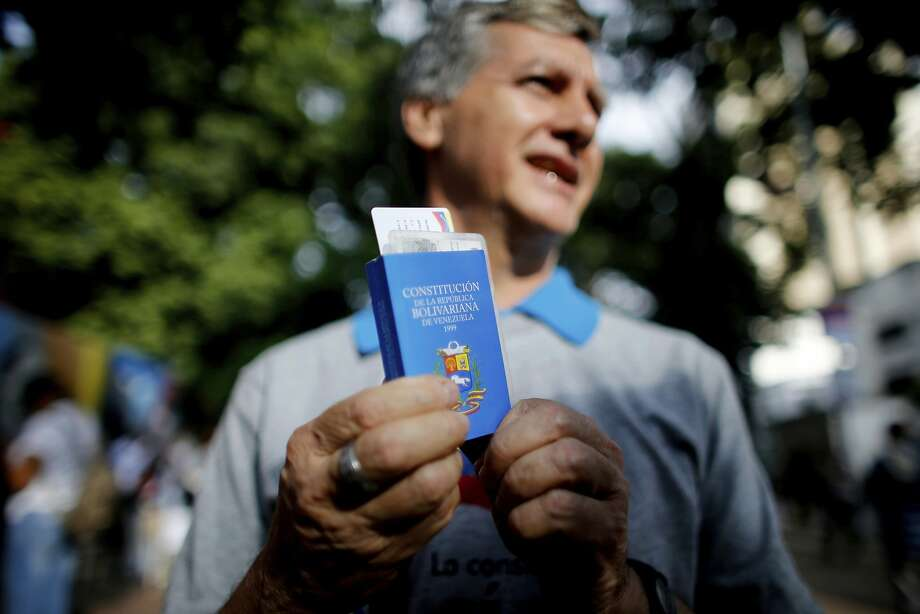 A voter holds a copy of the Venezuelan Constitution as he waits outside a polling station in Caracas. Photo: Ariana Cubillos, Associated Press