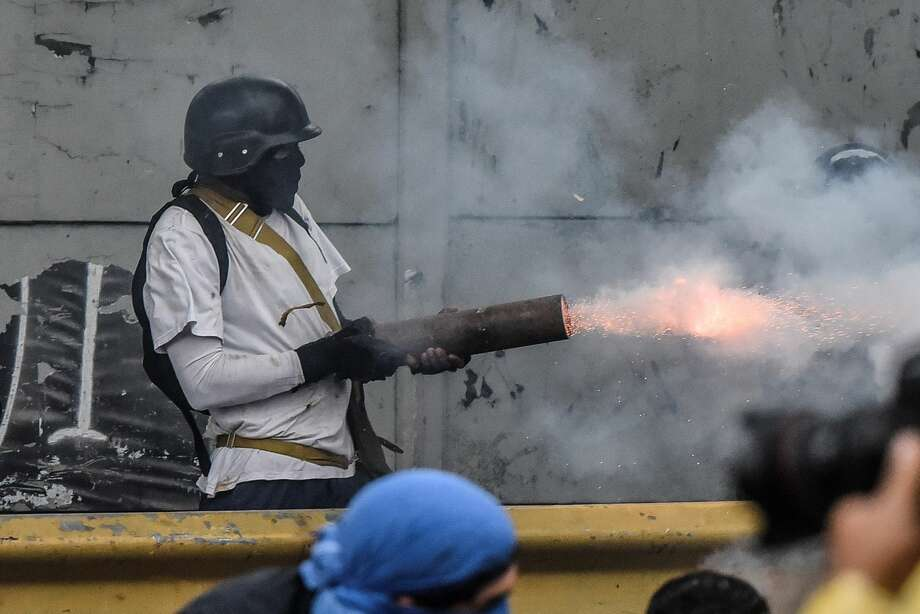 A protester shoots a firework from a pipe at the national guard members during clashes in Caracas, Venezuela on July 28, 2017. Protesters took over streets in Caracas on Friday in a show of defiance to President Nicolas Maduro, as the crisis gripping Venezuela turned deadlier ahead of a controversial weekend election that has earned international scorn.  Photo: Anadolu Agency/Getty Images